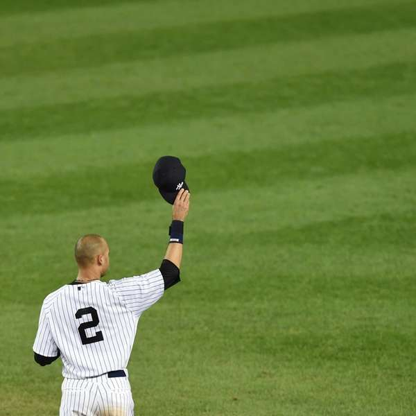 Derek Jeter tips his cap to the crowd after celebrating a walk-off single to win his final game at Yankee Stadium.