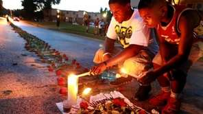 Ferguson residents light candles at a memorial for