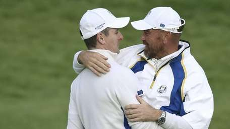 Europe's Thomas Bjorn congratulates Justin Rose on winning