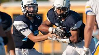 Oceanside QB Vincent Guarino, left, hands off to