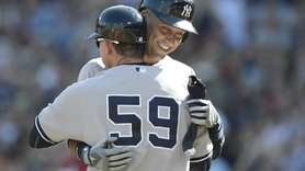 The Yankees Derek Jeter is hugged by third