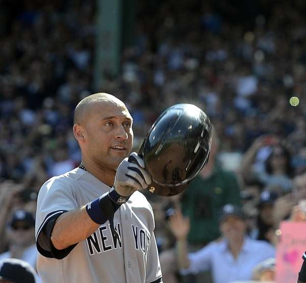 The Yankees' Derek Jeter waves to the crowd