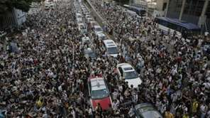 Thousands of people block a main road in
