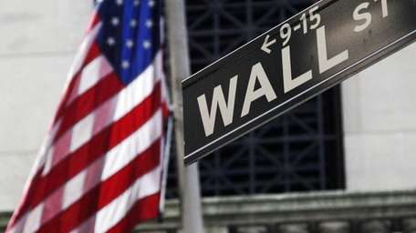 An American flag and Wall Street street sign