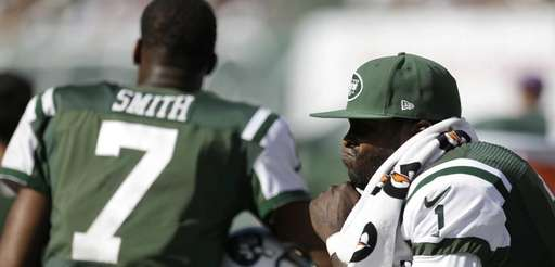 Jets quarterback Michael Vick, right, sits on the