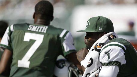 Jets quarterback Michael Vick, right, sits on the