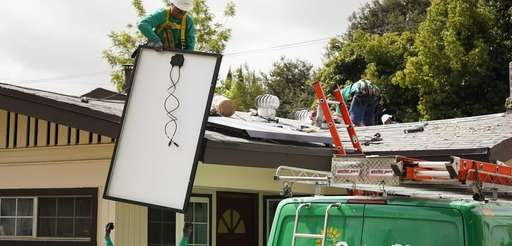 SolarCity Corp. employees lift solar panels onto the