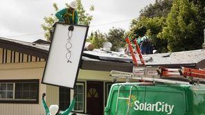 SolarCity Corp. employees lift solar panels onto the