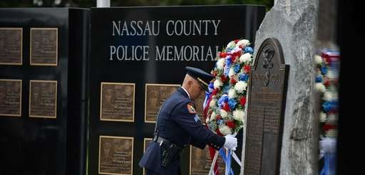 A police officer places a floral arrangement at