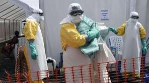 A health worker in protective suit carries equipment