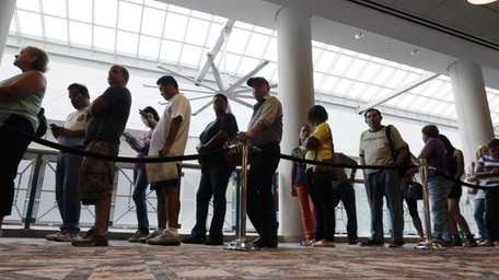 People wait in line to sign up for