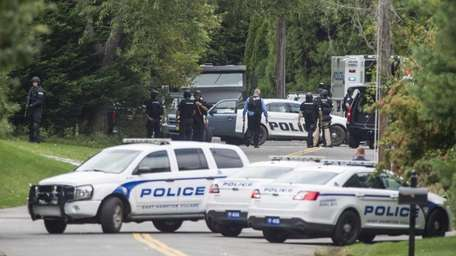 Police from several jurisdictions surround a home in