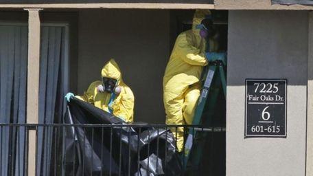 Hazardous material cleaners prepare to hang black plastic