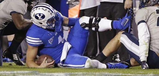 Injured BYU quarterback Taysom Hill holds his leg