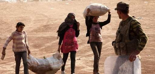 Newly arrived Syrian Kurdish refugees walk with their