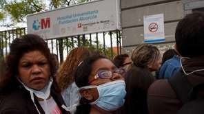 A woman and girl wear protective masks Tuesday,