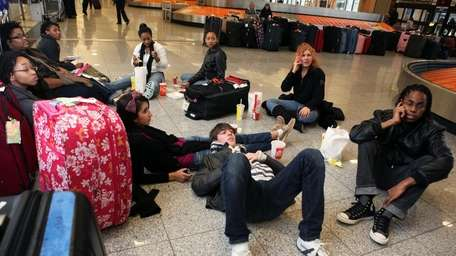 Passengers relax in the baggage claim area of
