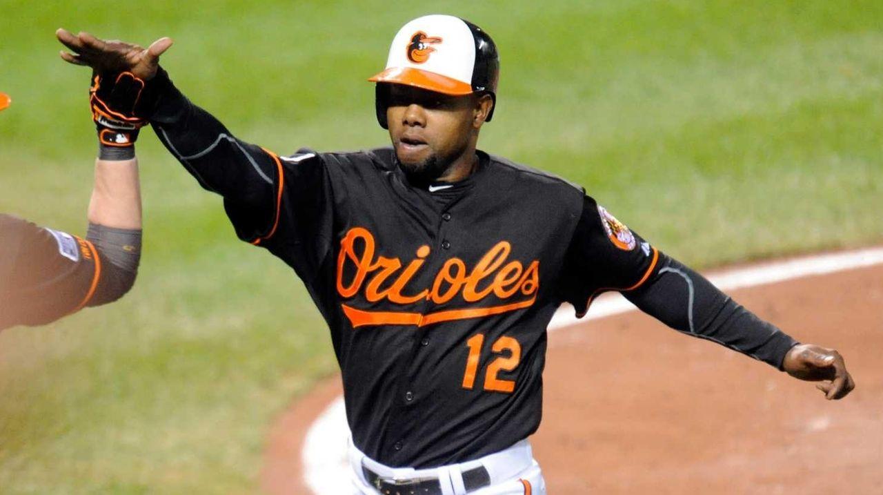 The Baltimore Orioles' Alejandro De Aza #12 scores