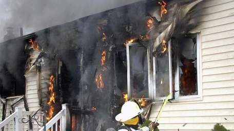 Firefighters work to put out a house fire