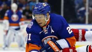 Kyle Okposo of the Islanders plays the puck