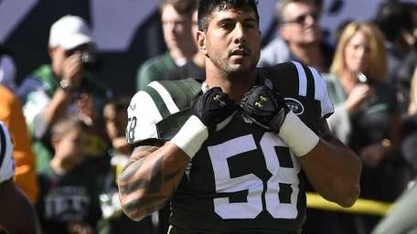 Jets defensive end Jason Babin stretches before a