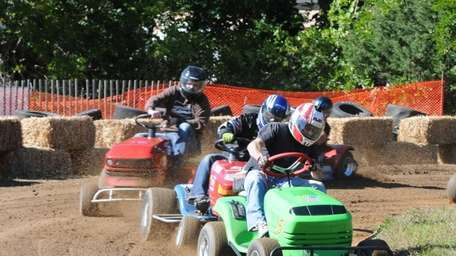Steve DeFriest, front, competes in a lawnmower race