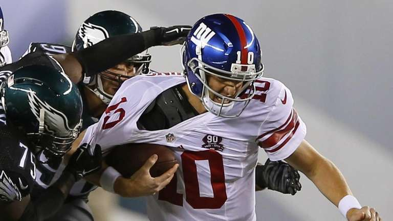 Giants quarterback Eli Manning, right, is hit by