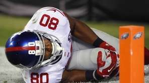 Giants wide receiver Victor Cruz holds his knee