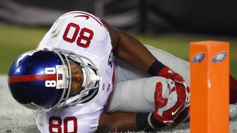 Giants wide receiver Victor Cruz holds his knee