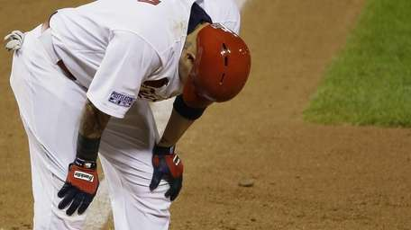 St. Louis Cardinals catcher Yadier Molina hunches over