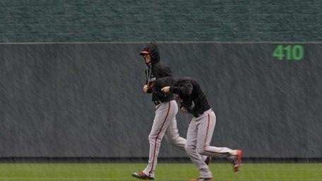 Baltimore Orioles players run as rain falls after