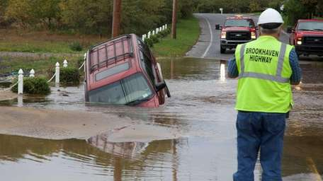 An SUV sits partially submerged in a sinkhole