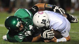 Farmingdale's Charlie Tomassetti, left, tackles Oceanside quarterback Vincent