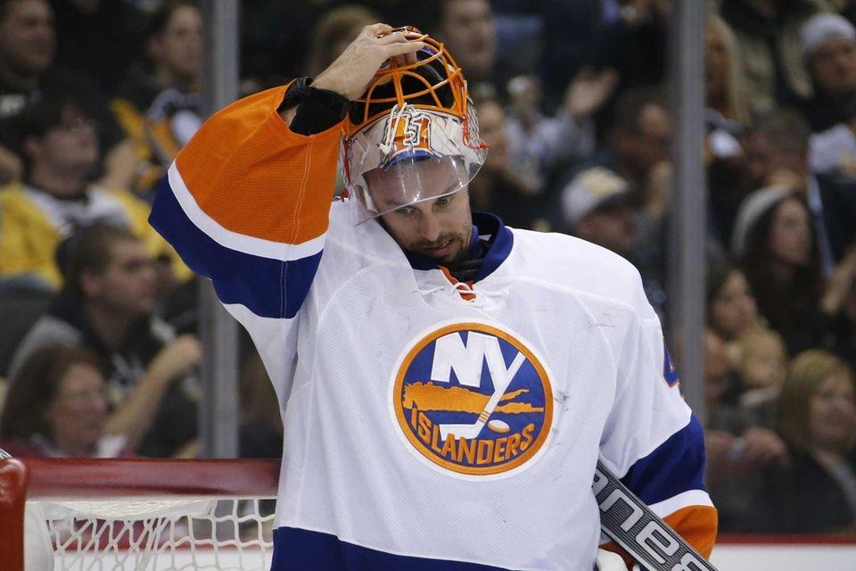 Islanders goalie Jaroslav Halak removes his mask after
