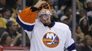 Islanders goalie Jaroslav Halak removes his mask after