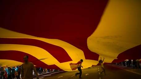 People walk under a huge Spanish flag as