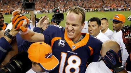 Denver Broncos quarterback Peyton Manning (18) celebrates his