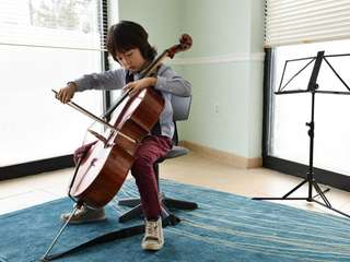 Justin Yu, 8, plays his cello at the