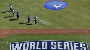 The Kansas City Royals grounds crew waters down