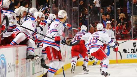 The Rangers celebrate the game-winning overtime goal by