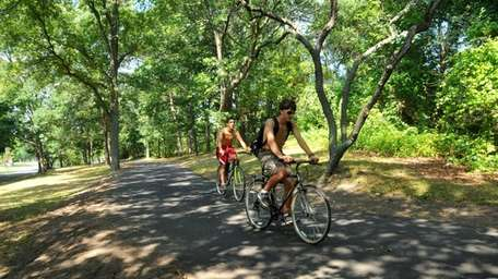 Bikers ride along the path at Bethpage State