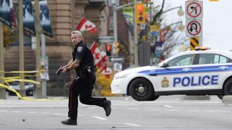 An Ottawa police officer runs with his weapon