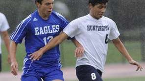 Hauppauge's Adam Moumine defends Huntington's Olvin Palma in
