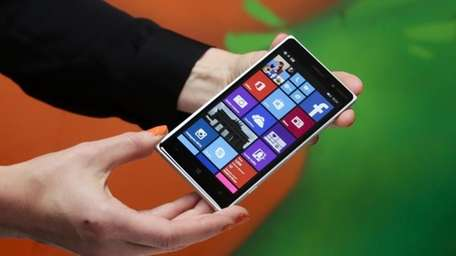 A woman shows the new Lumia 830 smartphone