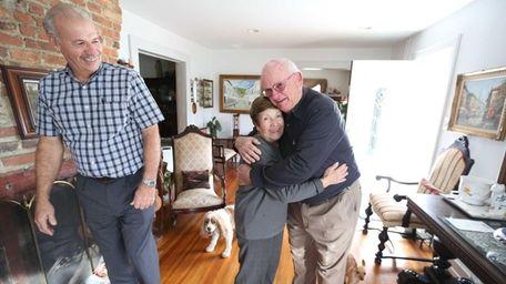 Amityville homeowner Margarita Caicedo hugs Bob Ellis, right,