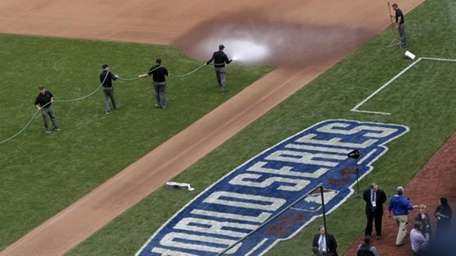 The grounds crew waters down the area near