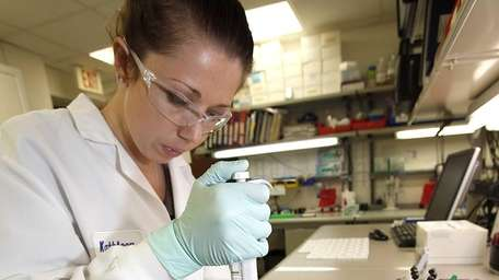 Scientist Kathleen Addiss uses a pipette to introduce