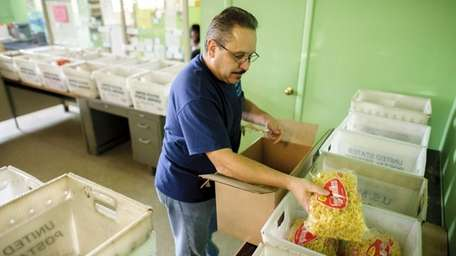 Mark Fernandez, of Oceanside, sorts food supplies on