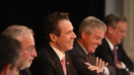 Governor Andrew Cuomo smiles during a press conference