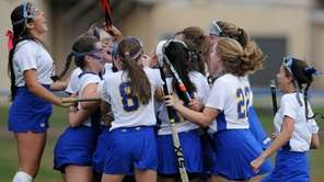 East Meadow teammates celebrate after their 2-1 overtime